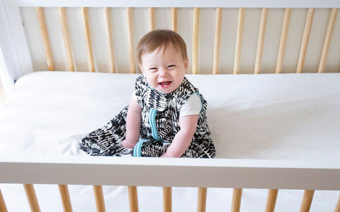 happy baby wearing MiliMili sleep sack in crib