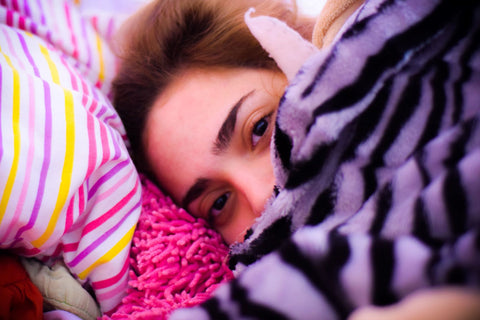 woman under pile of colorful blankets