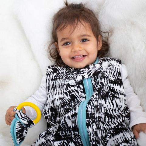toddler with small lovey in milimili black and white bamboo sleep sack