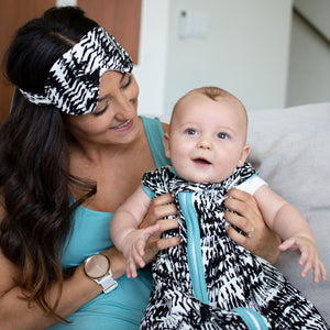 Mom with baby wearing black and white Kilauea sleep sack and matching eye mask for mama