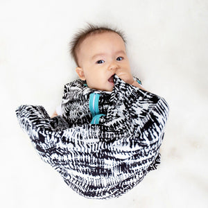 baby wearing black and white watercolor sleep sack with aquamarine contrast trim