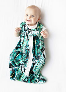 baby in palm print / banana leaf print sleep sack with white pompom trim
