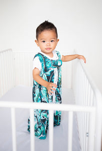 baby standing in white crib, wearing palm print / banana leaf print sleep sack with white pompom trim