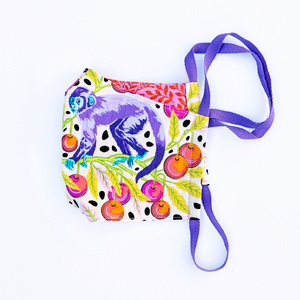 Colorful purple monkey and cherry print face mask with reversible red and pink floral print back.