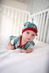 baby wearing milimili teal and red holiday bubbles sleep sack and bamboo baby beanie