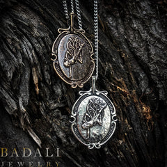a bronze and a silver version of the Ascendant Warrior Cameo on a background of tree bark