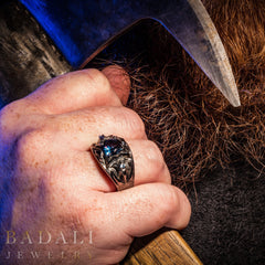 Dol Guldur Ring on a masculine hand, which is holding an axe.