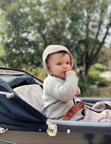 classic vintage style baby bonnet in merino cashmere blend with linen lining. Baby in vintage pram wearing bonnet.
