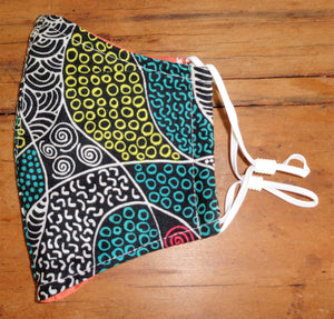 reusable fabric face mask fashion featuring an Australian Indigenous art design in red, green and white. Featuring adjustable elastic straps and popular during the 2020 Covid 19 pandemic.