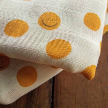 Load image into Gallery viewer, double muslin baby wrap featuring smiley faces in yellow. Decorate your nursery and nest for baby. Gifts.