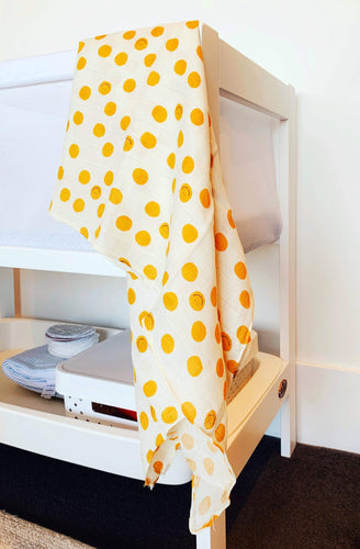 double muslin baby wrap featuring smiley faces in yellow. Decorate your nursery and nest for baby. Gifts.
