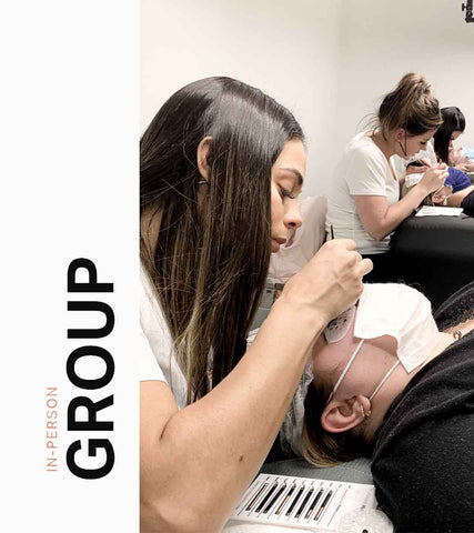 A group shot of several thelashbrand students in classroom, training on live models.