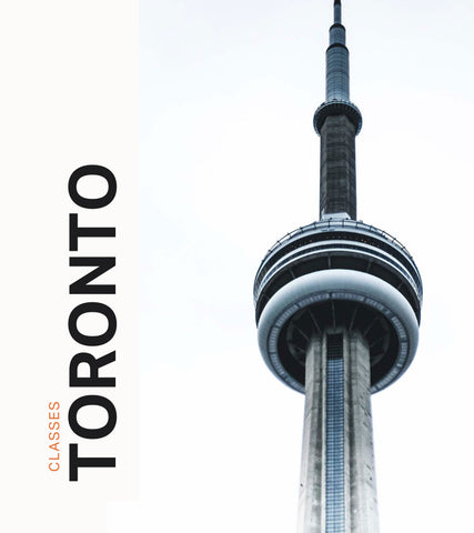Close up of the Toronto CN tower against a clear grey sky.