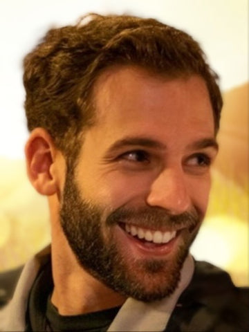 A handsome bearded man, smiling and turning his face toward the right.