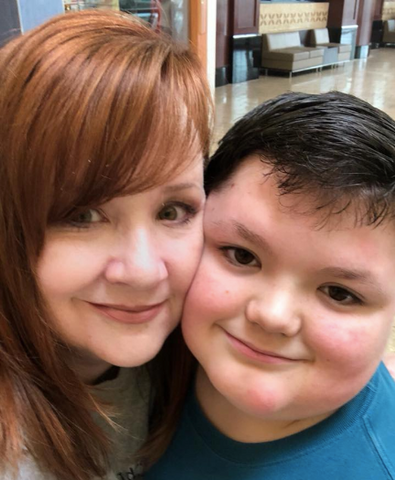 A smiling redheaded mother on the left and a handsome, cheeky young son on the right.