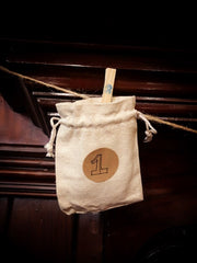Fabric pouch numbered with a handwritten number 1 and hung onto the string with a peg