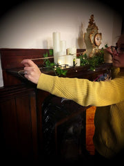 Shop Elf (staff member) measuring string over mantlepiece to hang the pouches