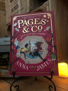 Image of the front of the hardback book Pages and Co: Tilly and the Map of Stories written by Anna James and illustrated by Paola Escobar. Displayed on a book stand with candles.