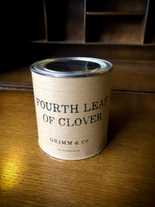 Image of Fourth Leaf of Clover green and gold shimmer ink sealed inside tin with lid closed and kraft paper label