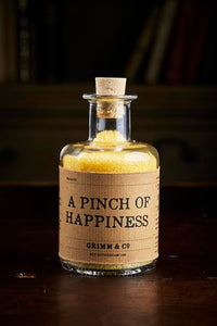 Image of A Pinch of Happiness otherwise known as scented yellow bath salts in a glass bottle with cork