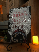 Load image into Gallery viewer, Image of front cover of paperback book Children of Blood and Bone stood in book stand with a candle