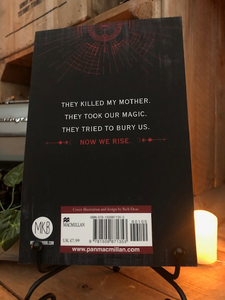 Image of back cover of the paperback book Children of Blood and Bone stood in book stand