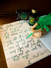 Load image into Gallery viewer, Image of Fourth Leaf of Clover green and gold shimmer ink displayed with a wooden mannequin gand and feather quill poised over paper with green cursive writing