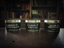 Load image into Gallery viewer, Image showing all three tinned candles in the Grimm & Tonic range including Glimmer of Confidence, Flicker of Fortune and Glow of Gratitude. Candles in silver tins with black labels and white text