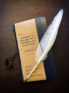Image of the midnight blue Journal of Dreams, Wild Schemes and Evil Plots, a vegan leather refillable journal with kraft label, pictured with the white biro quill.