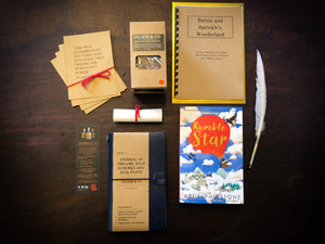 Image shows the contents of a Novel Tea Box laid out flat. The set shows a box of red berry tea, a midnight blue Journal of Dreams, the novel Rumblestar by Abi Elphinstone, a white biro quill, some printed quote cards on kraft card, a copy of Bernie and Sprinkle's Wonderland written by pupils of Canklow Woods Primary School, a bookmark and a scrolled certificate of awesome.