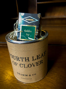Image of a tin of Fourth Leaf of Clover with kraft paper label and the box of ink poking out of the tin among wood wool shreds