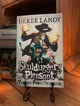 Load image into Gallery viewer, Image of the front of the paperback book Skulduggery Pleasant by Derek Landy. Displayed on a book stand.