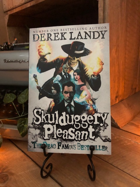Image of the front of the paperback book Skulduggery Pleasant by Derek Landy. Displayed on a book stand.