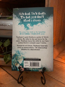 Image of the back of the paperback book Skulduggery Pleasant by Derek Landy. Displayed on a book stand.