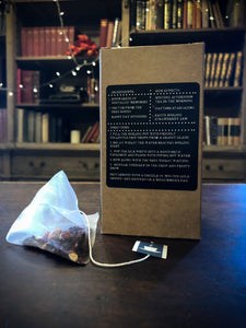 Image of the back of Grimm's Restorative Brew Box, a kraft box with black labelling containing 15 red berry silk tea temples, with one teabag laid out next to box.