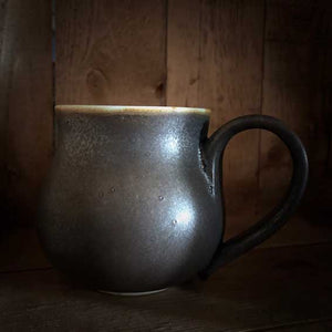 Image of a Travel Cauldron,  more commonly known as mugs in the mortal realm, ceramic and dyed a rich copper to black colour, each one is unique and handmade. The regular sized mug has the Grimm & Co 'G' monogram stamped into the base of the handle.
