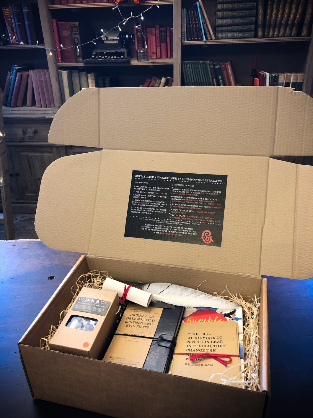 Image shows an open Novel Tea Box. A gift box bundle featuring the book Rumblestar by Abi Elphinstone. The set shows a box of red berry tea, a midnight blue Journal of Dreams, the novel, a white biro quill, some printed quote cards on kraft card and a scrolled certificate of awesome tucked within wood wool.