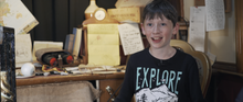 Load image into Gallery viewer, Image of a young boy looking excited and smiling, sat in Graham Grimm's office at Grimm & Co talking about our writing workshops
