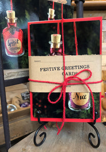 Image shows a pack of 8 festive greetings cards printed on glossy card. Images are of mini potion bottles with festive labels, tied with red twine and a kraft paper label