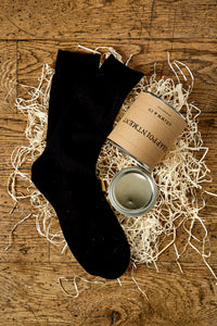Image of an example black sock next a tin of disappointment laying on its side in a nest of wood wool with the lid removed.