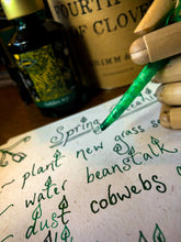 Load image into Gallery viewer, Image of Fourth Leaf of Clover green and gold shimmer ink displayed with a wooden mannequin gand and feather quill poised over paper with green and gold shimmer cursive writing