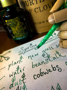 Image of Fourth Leaf of Clover green and gold shimmer ink displayed with a wooden mannequin gand and feather quill poised over paper with green and gold shimmer cursive writing