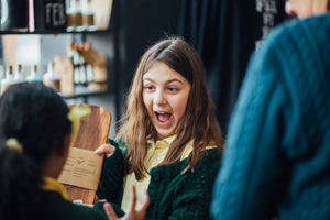 Image of a happy school girl looking at items in the shop after attending her first Grimm & Co writing workshop
