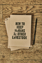 Load image into Gallery viewer, Image shows a few kraft card notebooks in a pile with the top one displaying the slogan HOW TO KEEP HUMANS & OTHER LIVESTOCK'. Notebooks are shown with a Word Wand pencil.