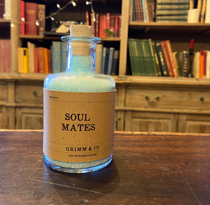 Image of a glass potion bottle filled with pale blue bath salts. The bottle label reads: Soul Mates.