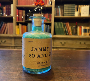 Image of a glass potion bottle filled with pale blue bath salts. The bottle label reads: Jammy So and So.