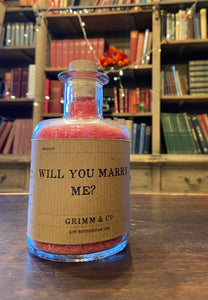Image of a glass potion bottle filled with red bath salts. The bottle label reads: Will You Marry Me?