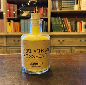 Image of a glass potion bottle filled with yellow bath salts. The bottle label reads: You Are My Sunshine
