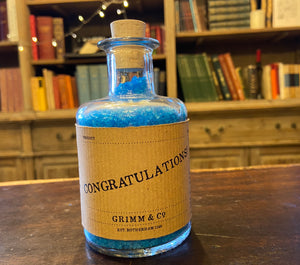 Image of a glass potion bottle filled with deep blue bath salts. The bottle label reads: Congratulations!