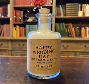 Image of a glass potion bottle filled with white bath salts. The bottle label reads: Happy Wedding Day Mr and Mrs Smith, 8th June 2020.